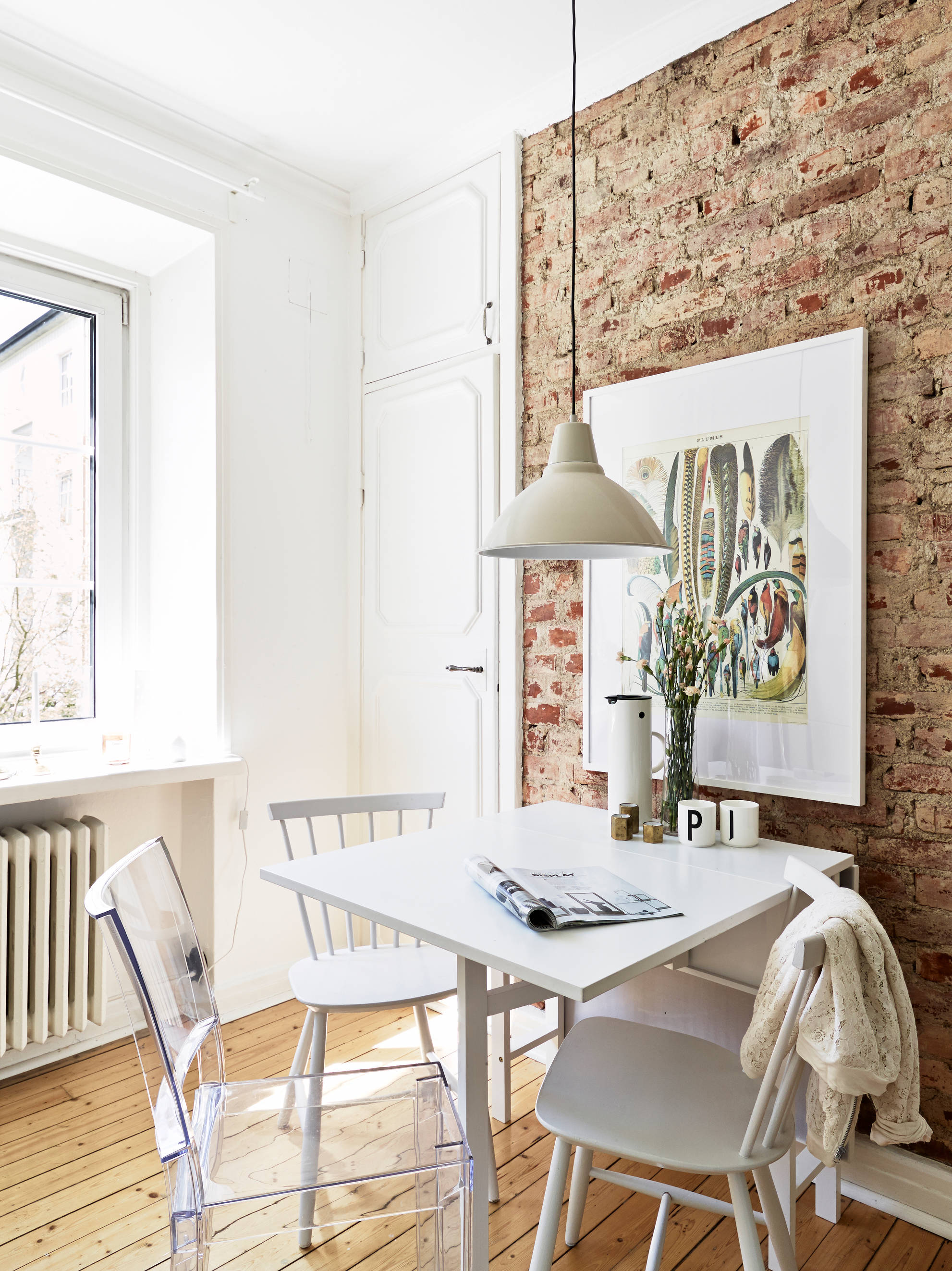 Постер и часы на белой кирпичной стене над обеденной зоной