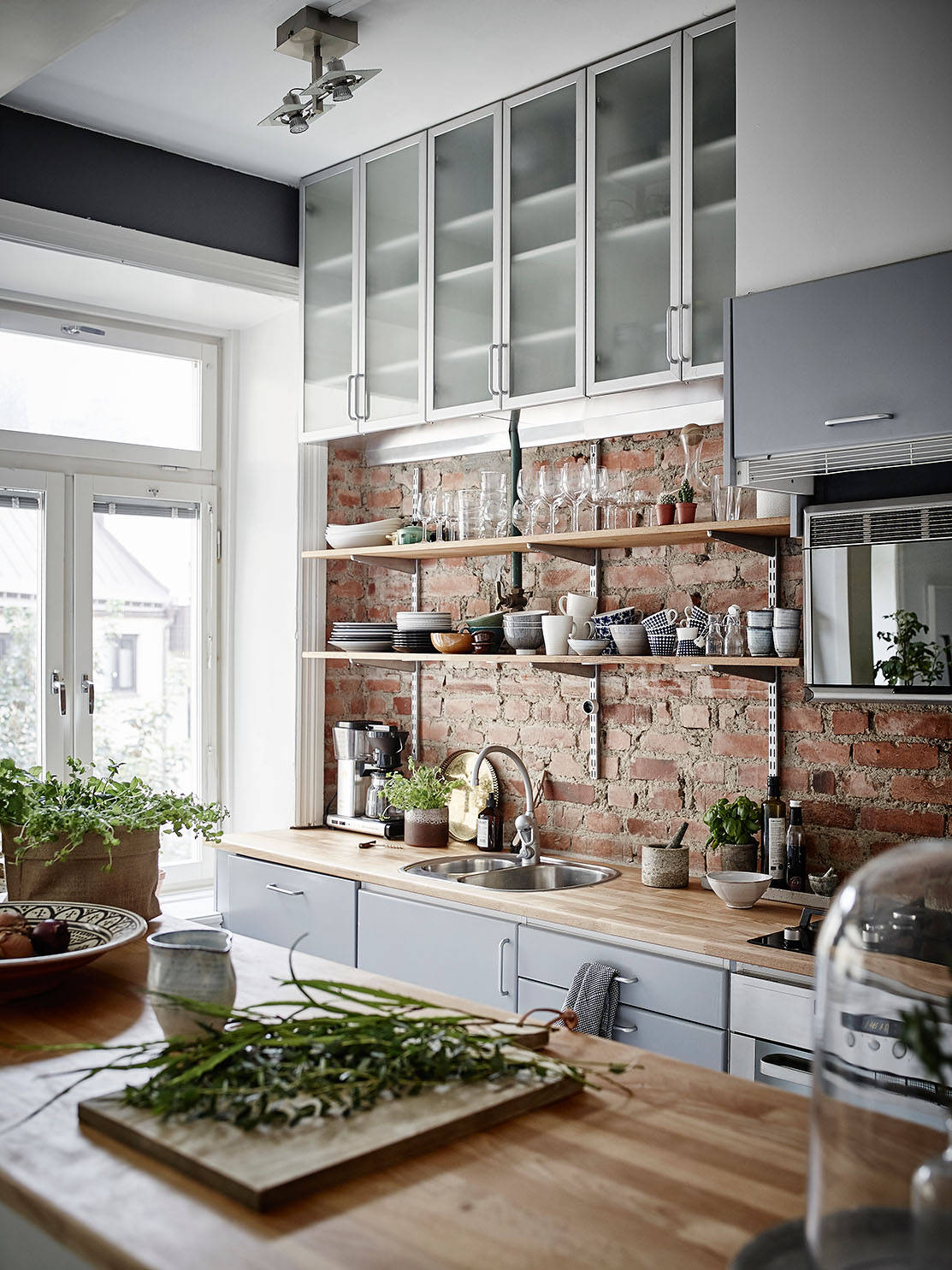 Cosy kitche interior · black kitchen furniture · red brick backsplash · kitchen brick wall